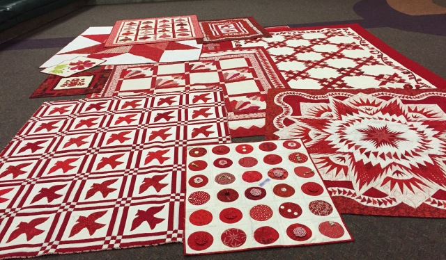 Red and white quilts waiting to be hung.