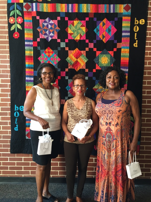 "Judges of the 2015 Atlanta Quilt Festival juried  quilt exhibit pose in front of ""Be Bold"""